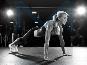 A muscular women doing push ups in a fitness club.